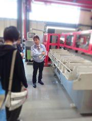 切断工場で機械による切断の精度の違いについて説明してくださる木村常務様
